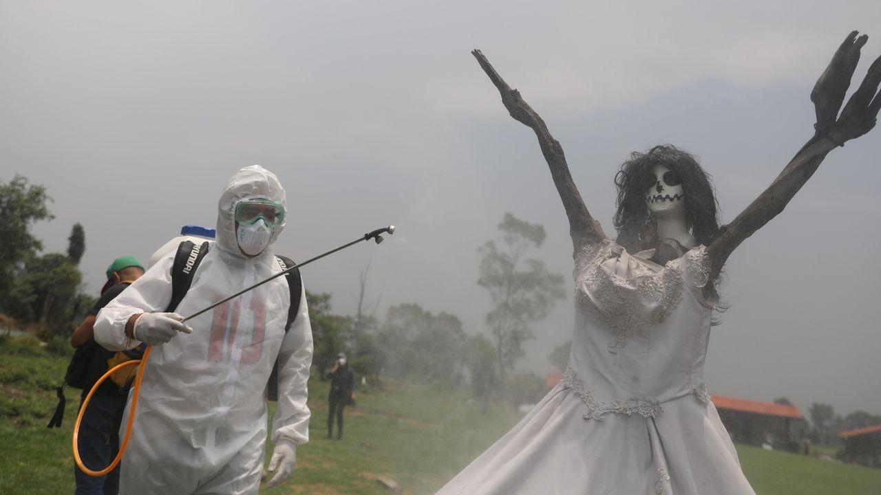 Un trabajador con traje de bioseguridad desinfecta, como medida de protección contra la pandemia, un árbol caracterizado como la Santa Muerte en un área de las Chinampas, en México