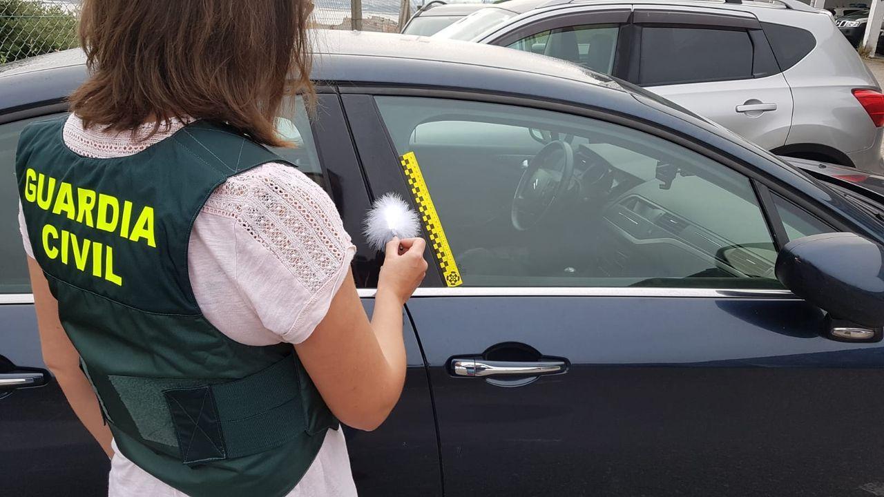 Una agente de la Guardia Civil busca huellas dactilares en un vehículo.Breixo, Saúl y Xes confían en poder retomar la actividad del local en el mes de julio