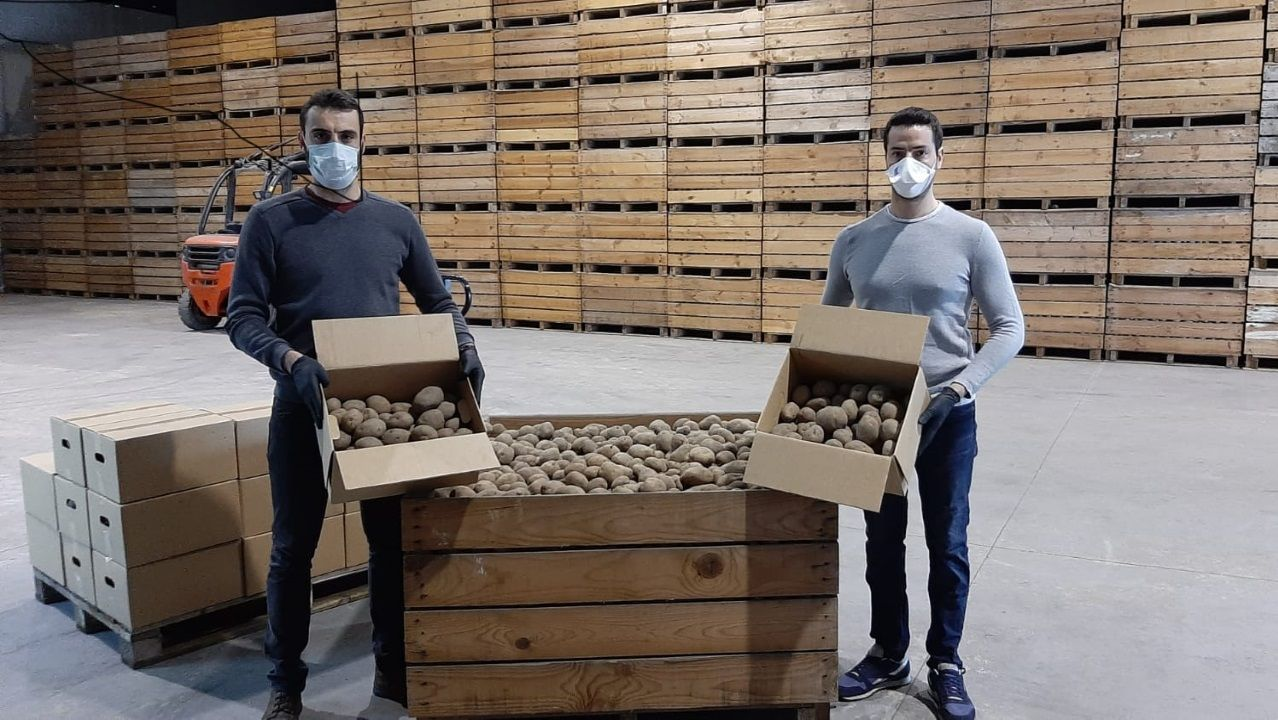 Primer día de mercado en Betanzos.Los hermanos Eloy y Raúl muestran las cajas de patatas que enviarán a los hogares
