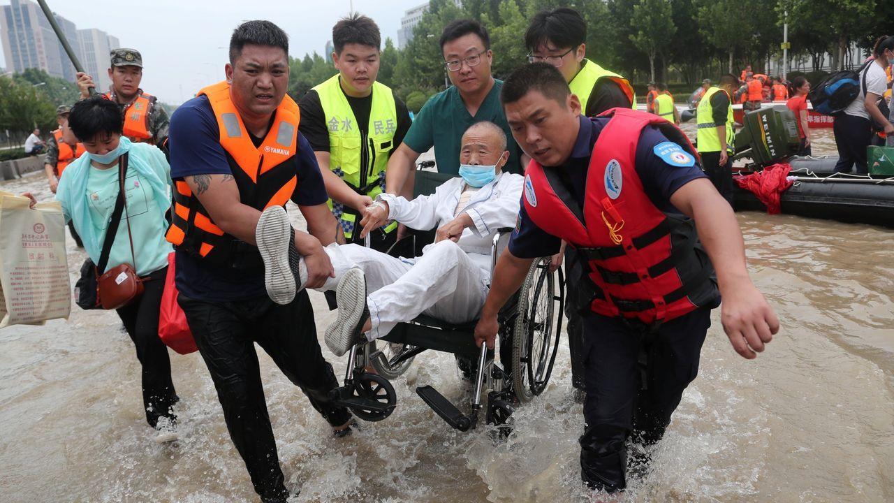 Equipos de rescate evacúan a una persona en silla de ruedas en la ciudad de Zhengzhou