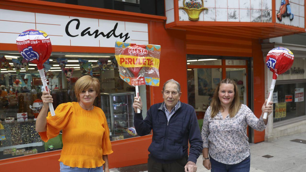 El fundador de Candy posa junto a sus actuales dependientas, Mercedes Villar (izquierda) y Olaya Iglesias (derecha), delante de la reconocible tienda de golosinas.  Ambas suman años y vivencias tras el mostrador: «Adultos que eran niños en los 80 regresan ahora con sus hijos».