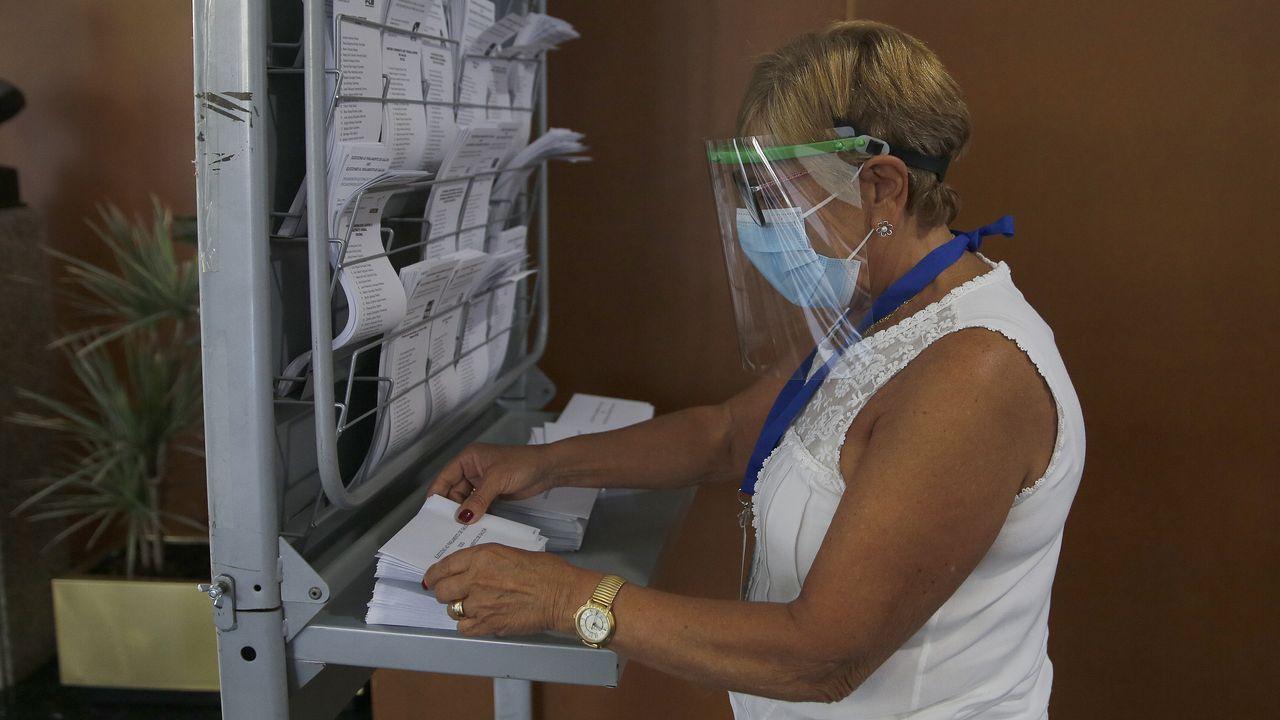 Una mujer, protegida, escogiendo su papeleta en A Coruña