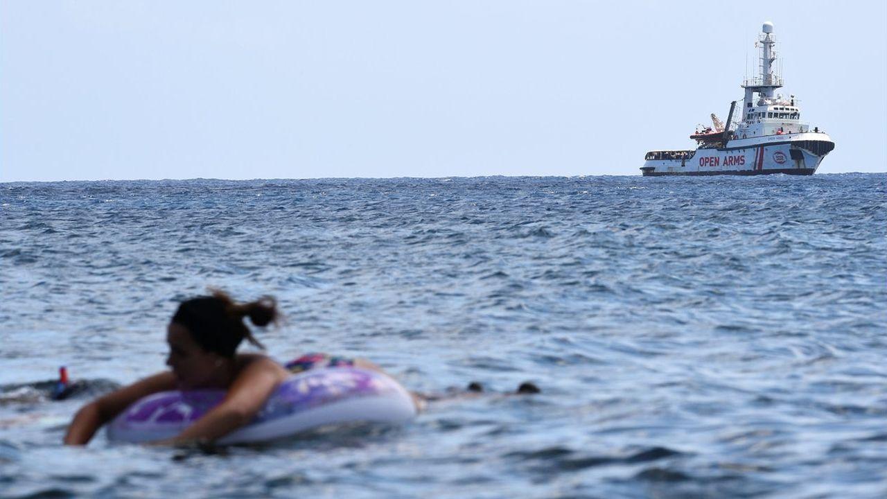 Una bañista, en una playa de Lampedusa, con el Open Arms fondeado al fondo a la espera de atracar en el puerto italiano