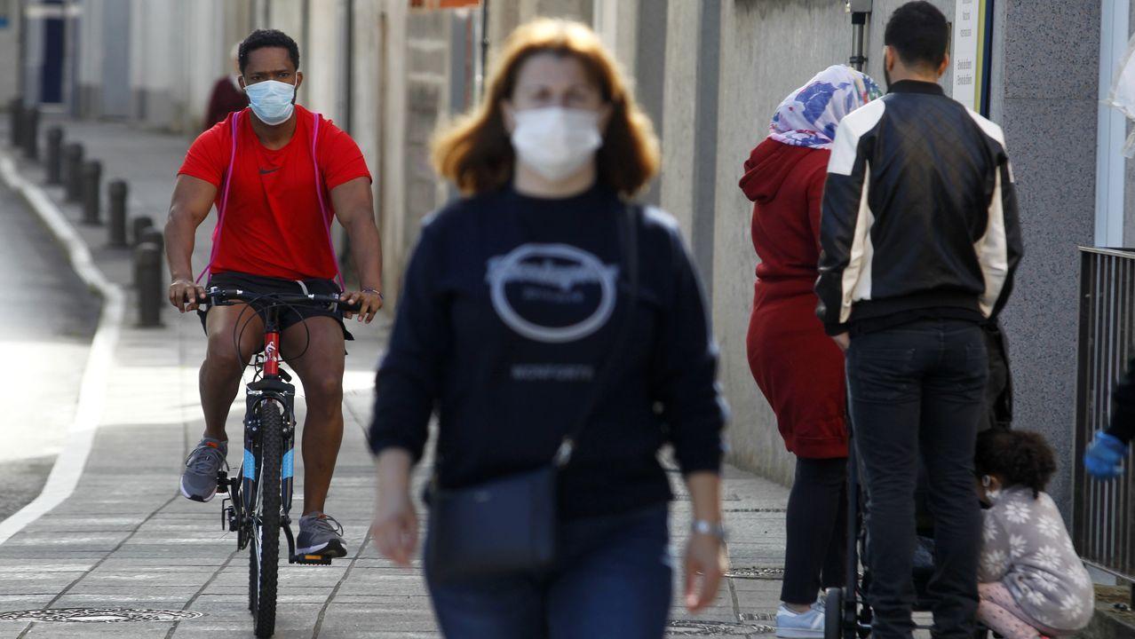 Un ciclista pasa junto a los peatones por la acera de una céntrica calle el primer día de la fase 1