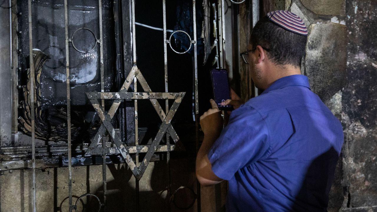 Los bombardeos israelíes castigan Gaza.Un judío israelí observa los daños en una sinagoga incendiada en la ciudad mixta de Lod