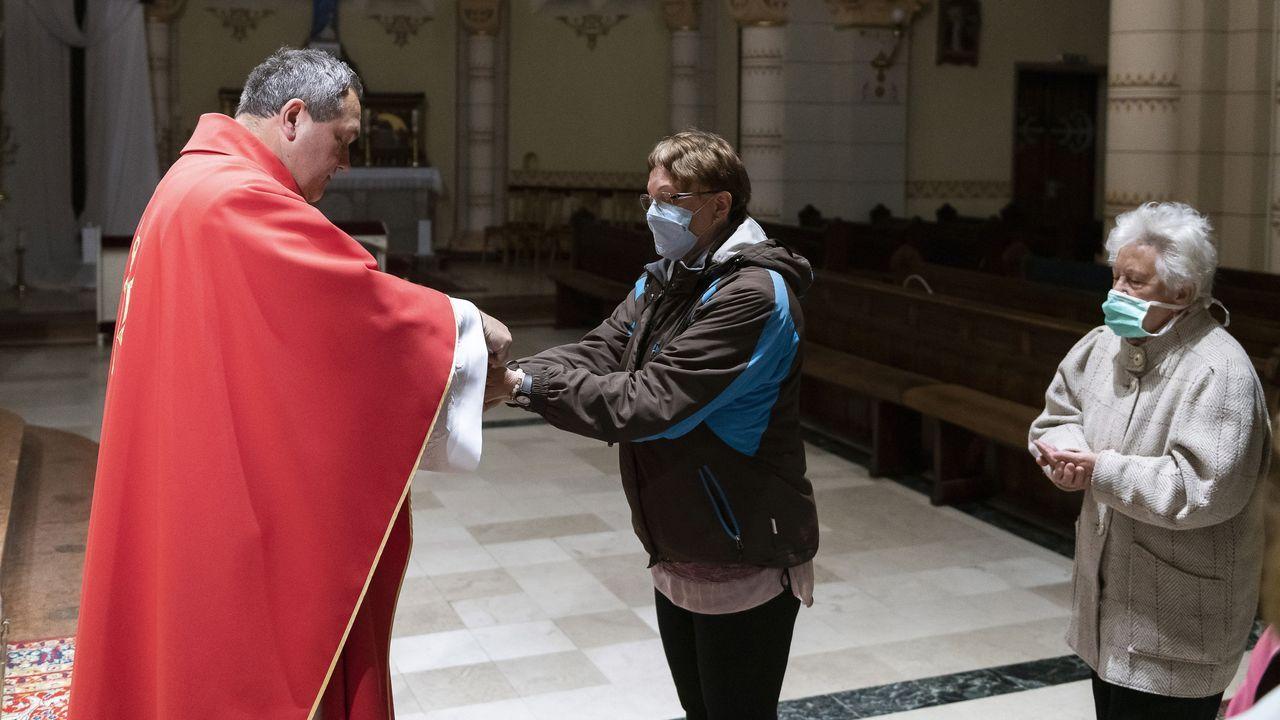Un sacerdote húngaro da la comunión a sus feligreses, ataviados con mascarilla