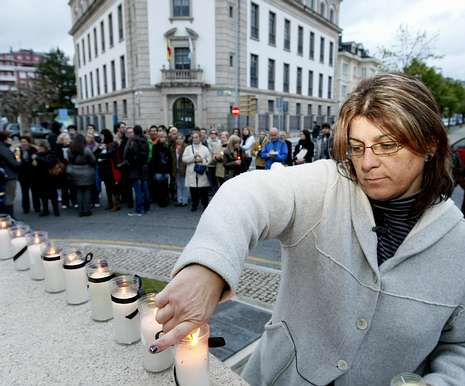 Isabel López, enciende velas en homenaje a las víctimas.