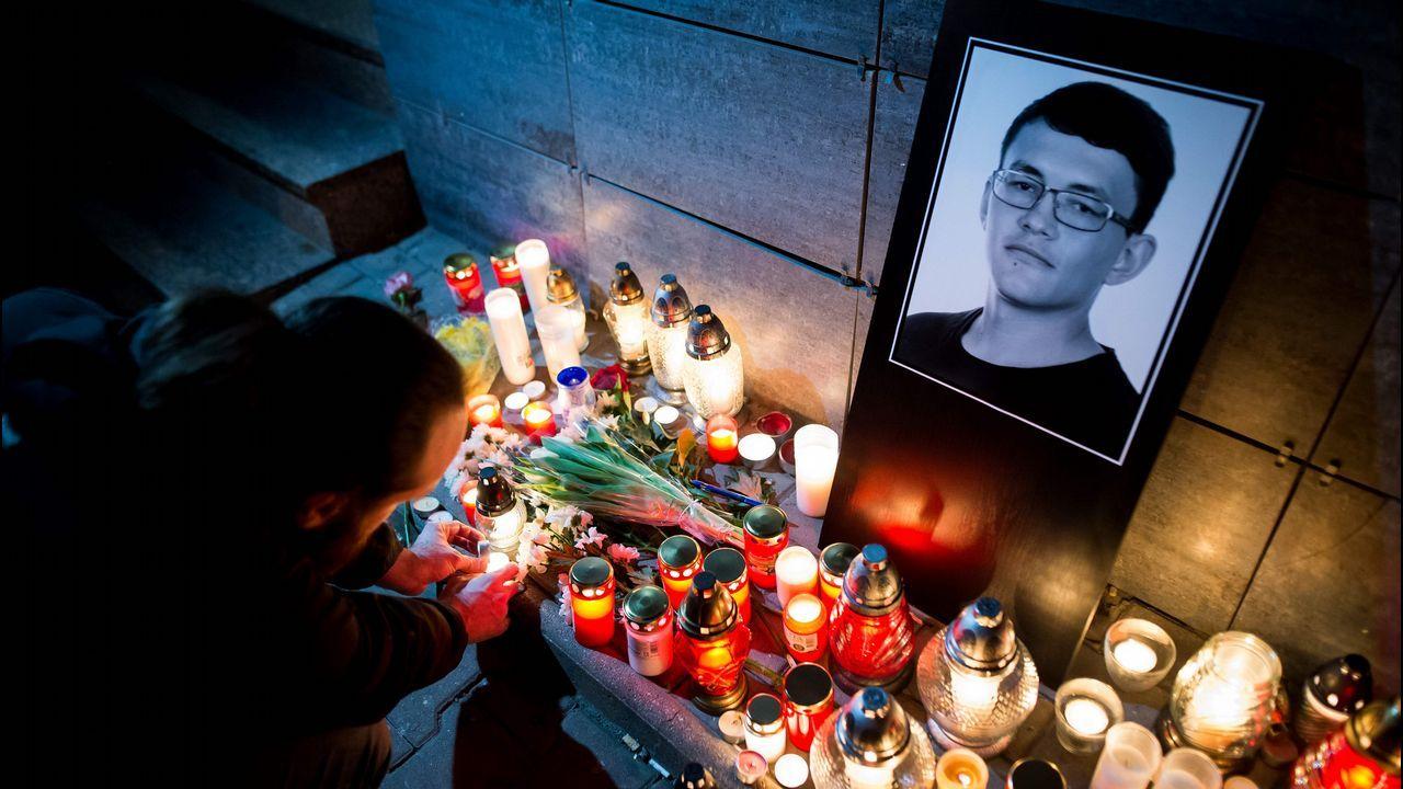 Un hombre enciende una vela enfrente de la sede de Aktuality Newsroom en recuerdo del periodista de investigación Jan Kuciak, que trabajaba indagando sobre empresarios corruptos en Eslovaquia.