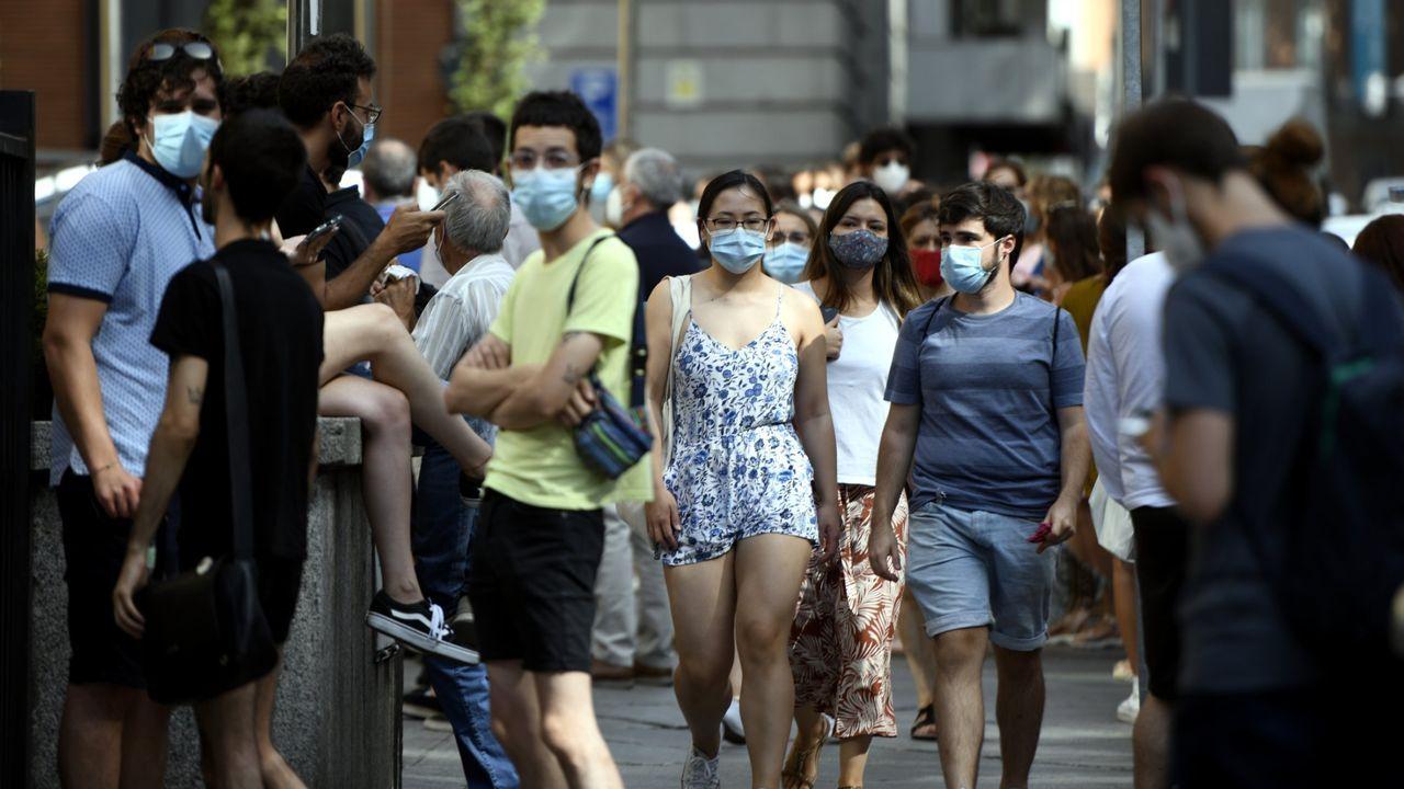 Se busca a las dos personas que huyeron a pie del accidente mortal.Varias personas con mascarilla en una calle del centro de Madrid