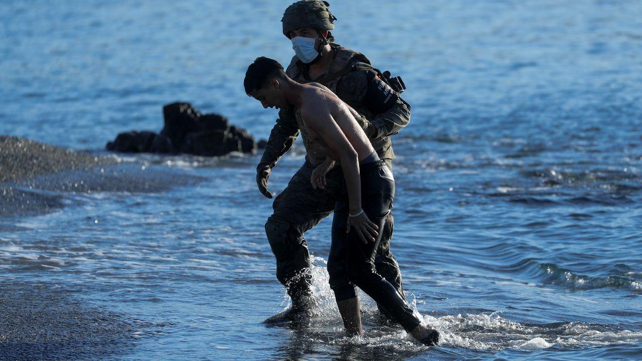 Un militar ayuda a un joven marroquí a su llegada a la playa