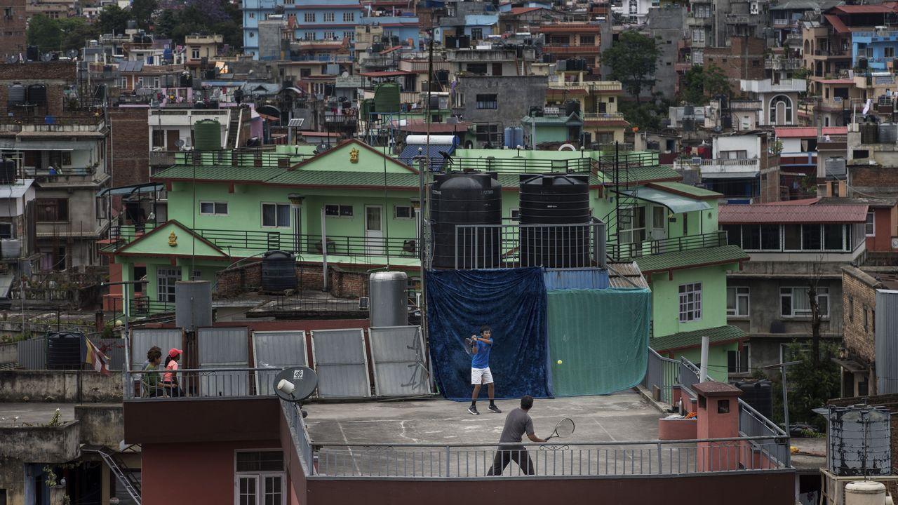 Un padre y un hijo juegan al tenis en la azotea de una vivienda en Katmandú, durante el confinamiento
