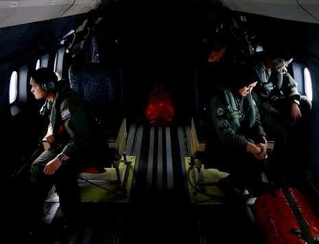 Miembros de las Fuerzas Aéreas malasias rastrean el mar desde una aeronave.