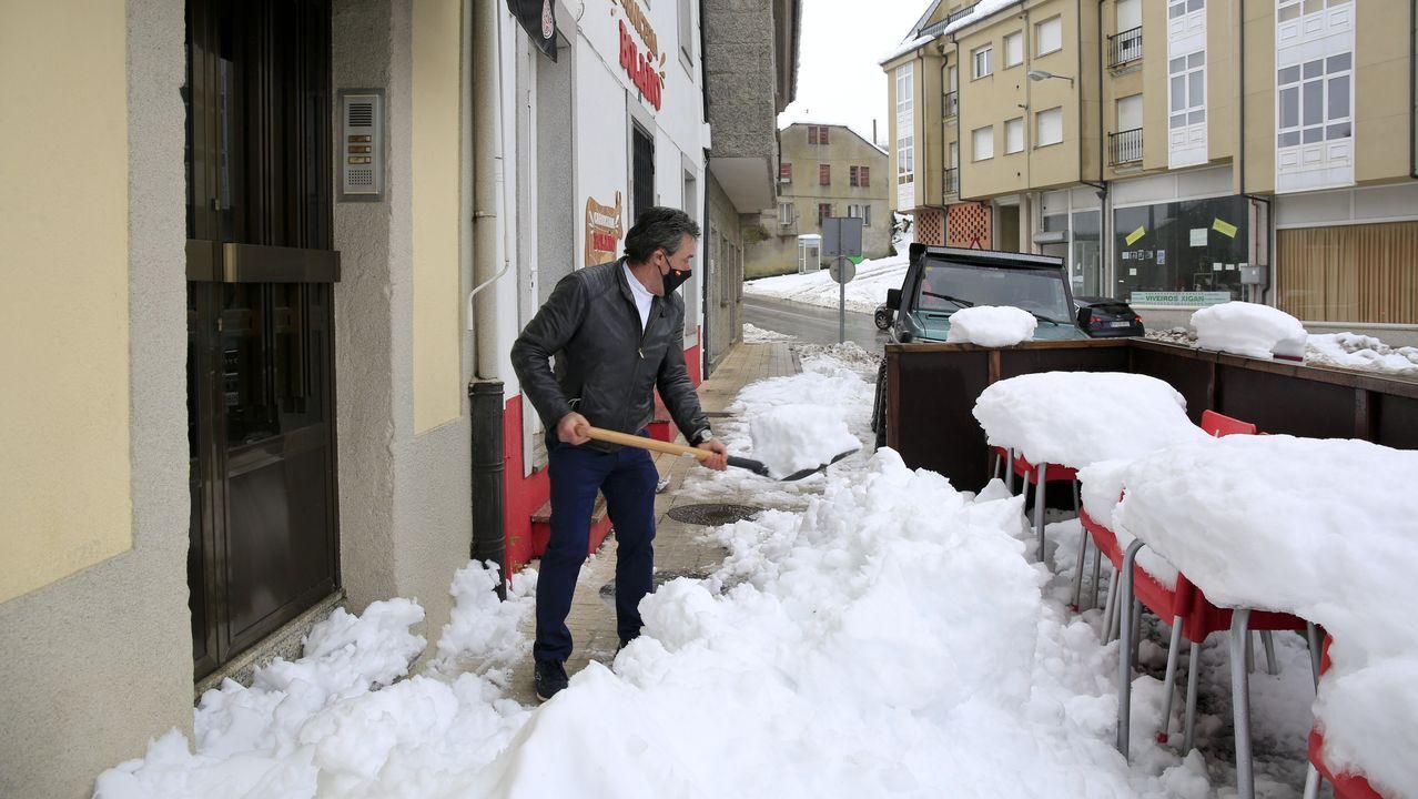 Una semana con cortes de luz en San Xián de Barrañán.El propietario de un bar de O Cádavo limpiando de nieve la entrada de su negocio, sin suministro eléctrico este domingo