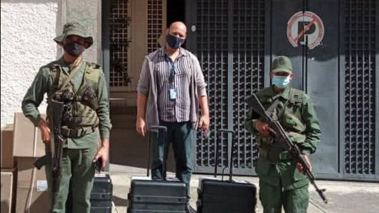 Un miembro de la Hermandad Gallega de Caracas, junto a los militares, en el colegio Castelao