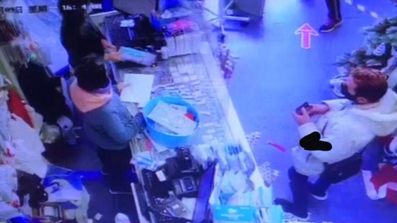 El detenido, a la derecha, con mascarilla, adquiriendo un cuchillo en un supermercado; el objeto lo tiene una dependienta, a la izquierda