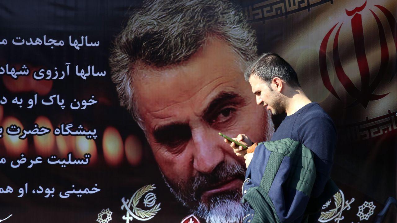 Ruedas de prensa posteriores a la Sesión de Investidura.Un hombre camina ante un enorme cartel con la imagen del general Soleimani en una calle de Teherán