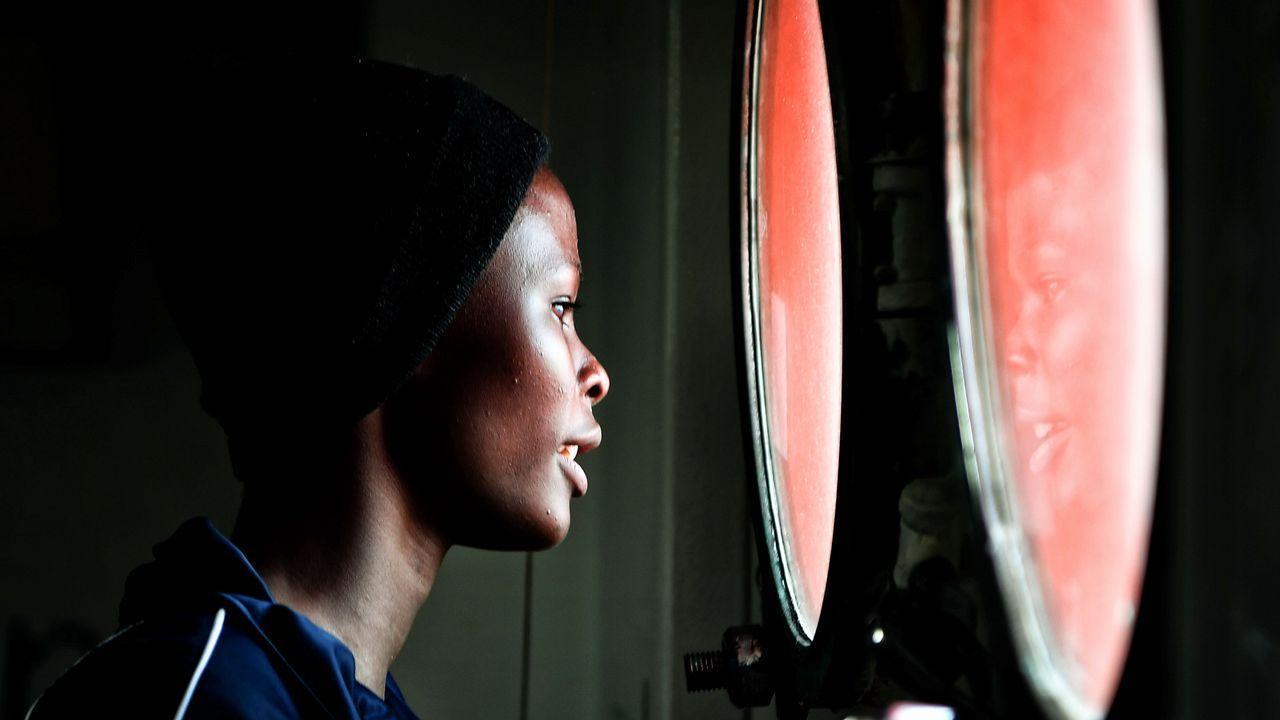 Una mujer  mira por un ojo de buey en el barco MV Aquarius, que rescató el pasado día 12 a 76 migrantes de distintas nacionalidades en el Mediterráneo