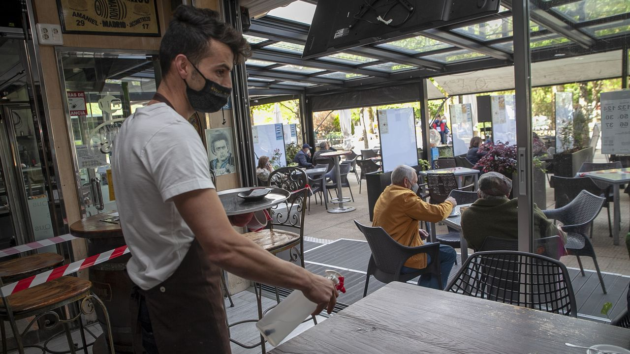 Pablo Martínez desinfecta una mesa dentro de su local, ya que en Noia pueden usar el 30 % del aforo interior