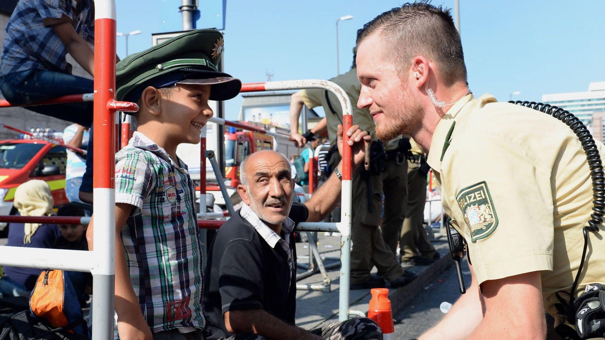 Trump visita a sus tropas en Iraq.Un policía alemán con refugiados sirios en Múnich, en la crisis migratoria del 2015