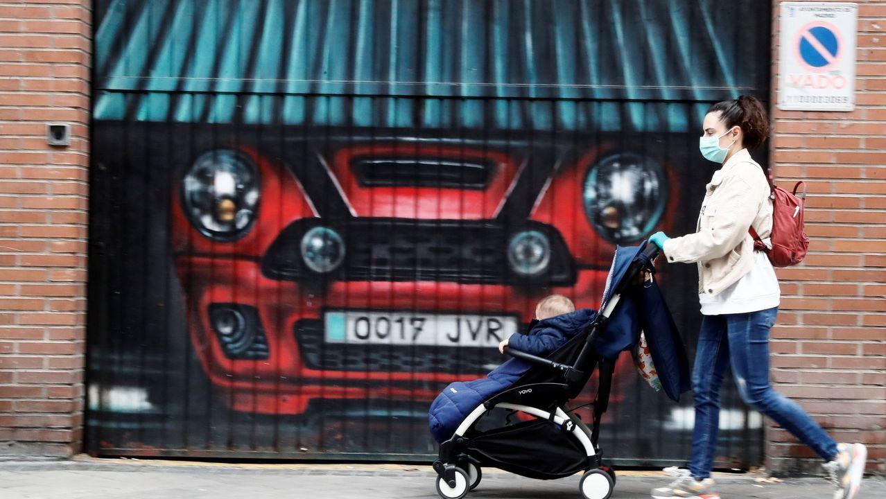 Una mujer empuja un cochecito de bebé por una calle de Madrid este domingo