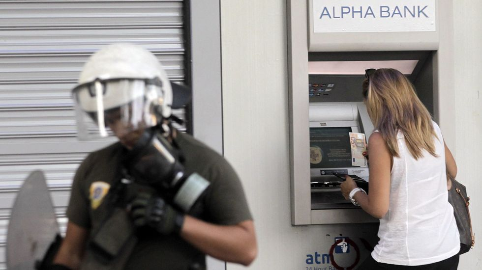 Manifestaciones multitudinarias en Atenas por el referendo.Una mujer custodiada por un policía mientras saca efectivo de un cajero automático en las calles de Atenas.