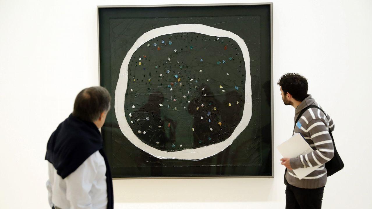 Dos visitantes observan el cuadro «Concepto espacial, La luna de Venecia 1961»