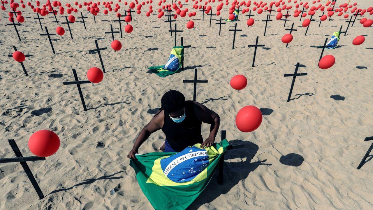 Imágenes de la pandemia en el mundo.Un hombre instala una bandera de Brasil en una representación escénica de la ONG Río de Paz por las 100.000 víctimas mortales del covid en el país