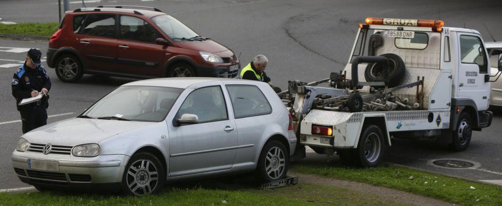Un policía local multa un coche mal aparcado mientras lo retira la grúa.