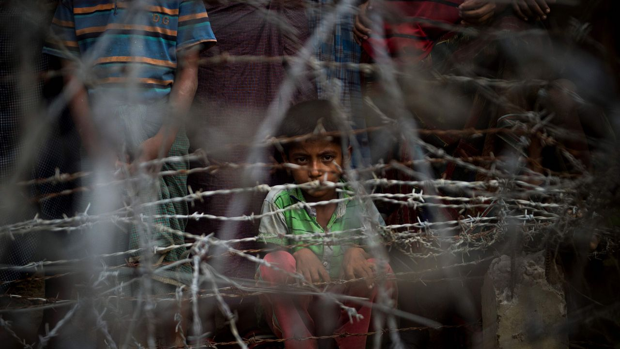 Niños refugiados rohingya tras una zona alambrada en Myanmar