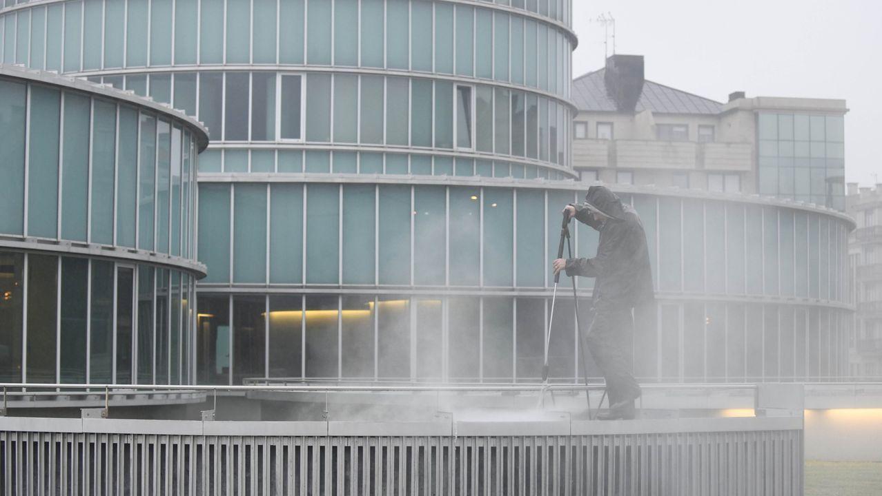 Un operario limpia la fachada del ayuntamiento de Lalín