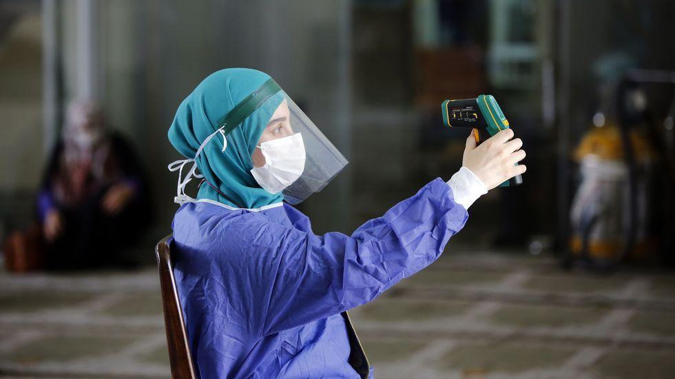 Un sanitario iraní comprueba su propia temperatura