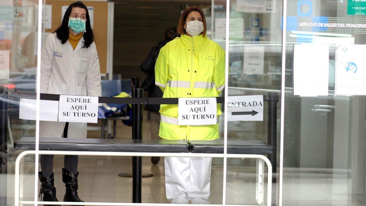 Coia se viste de fiesta por la noche.Personal sanitario controla el acceso al Centro de Salud de Puerta de la Villa, en Gijón