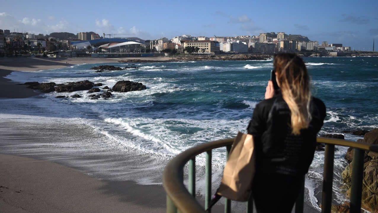 En la costa olas de siete metros y en el interior, nieve a 900 metros.Un grupo de personas con paraguas en La Escandalera de Oviedo