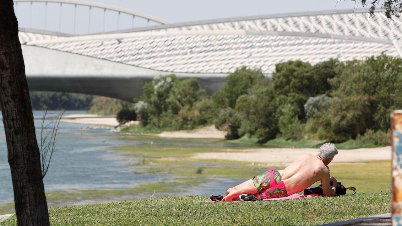 Un hombre toma el sol en la rivera del Ebro