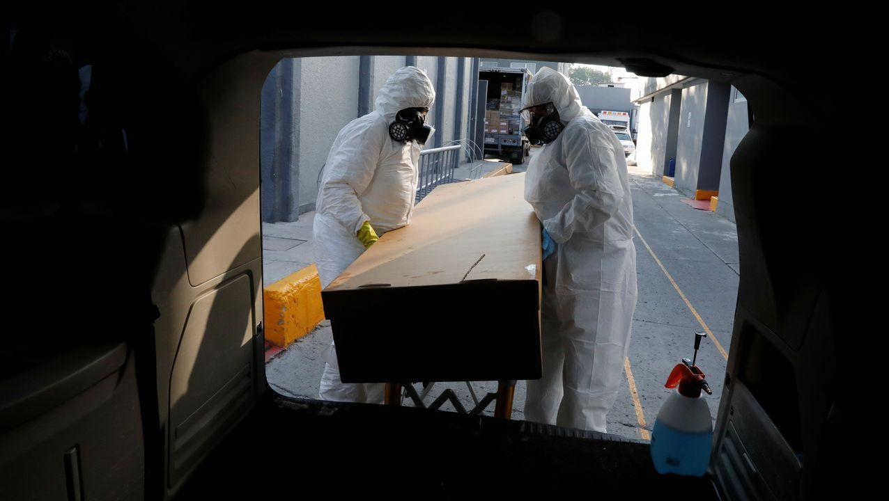 Trabajadores de una funeraria de Ciudad de México transportan el féretro de un fallecido por covid-19