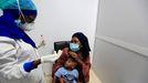 Una mujer y su hijo escuchan a una sanitaria que les realizará la prueba para detectar el covid-19 en Dakar, Senegal