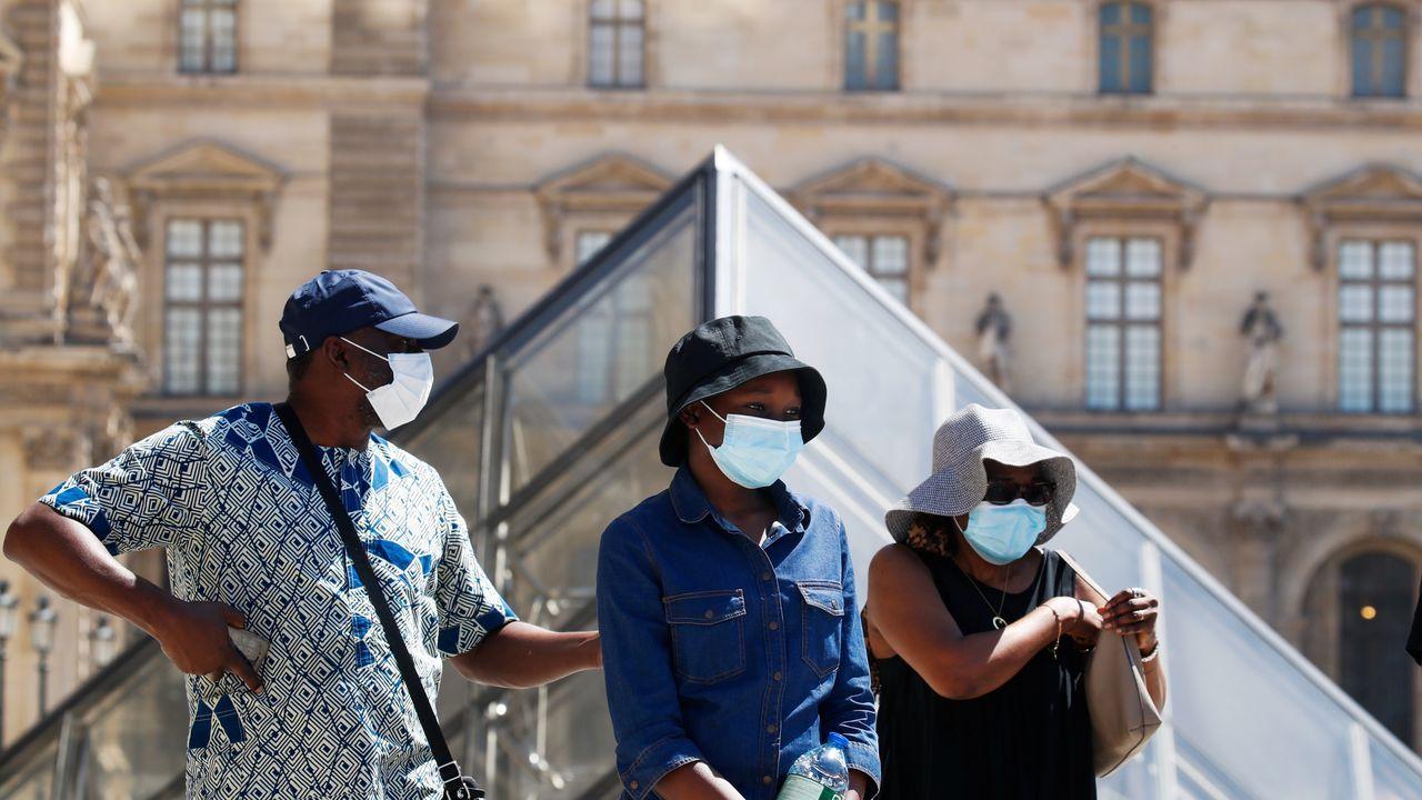 Personas con máscaras protectoras caminan cerca del Museo del Louvre, en París, mientras Francia refuerza el uso de máscaras como parte de los esfuerzos para frenar el resurgimiento del coronavirus en todo el país