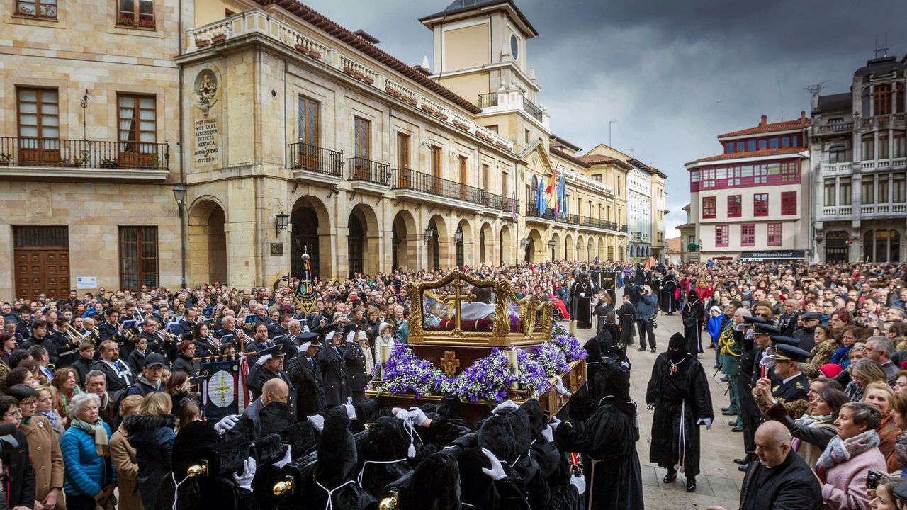 La imagen del Santo Cristo Yacente en la salida de la Iglesia de San Isidoro el Real, de la cofradia del Santo Entierro y Nuestra Señora de los Dolores, al inicio de la procesión hoy Viernes Santo en Oviedo dentro de los actos de la semana santa ovetense.