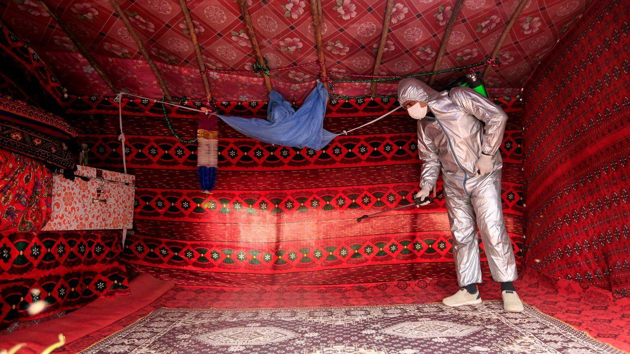 Un voluntario desinfecta una tienda improvisada en Jalalabad, Afganistán