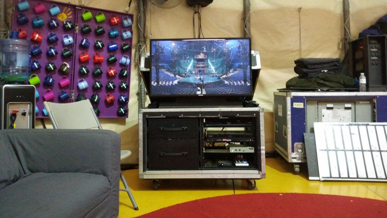 Kooza.El área de descanso en el backstage, con un televisor que muestra el escenario en tiempo real