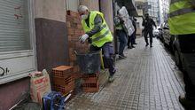 Un albañil tapia la puerta de una vivienda que fue okupada, en A Coruña
