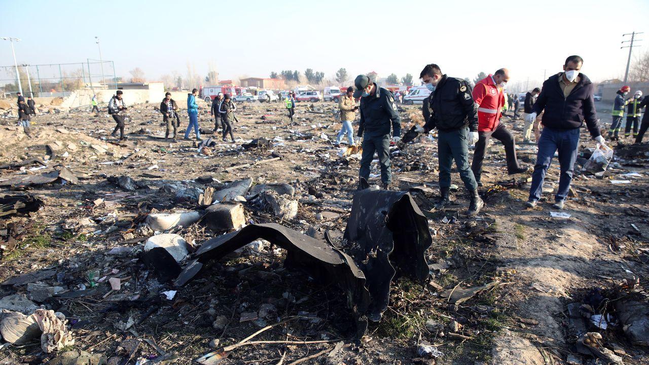 Agentes de emergencias inspeccionan los restos del avión derribado poco despues de su despegue en Teherán.