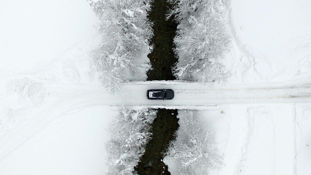 Una vista aérea muestra un coche cruzando un puente mientras la calle está cubierta de nieve en Untertauern, Austria