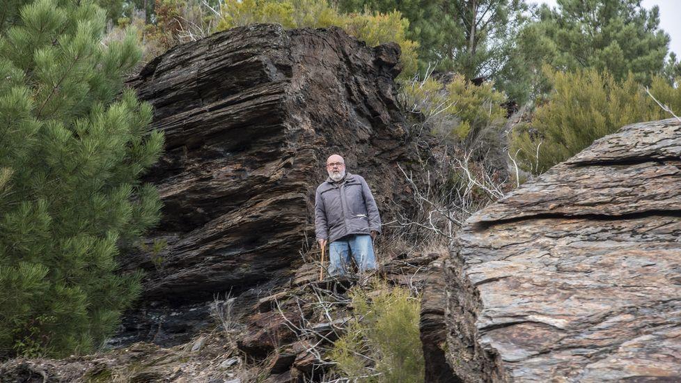 El profesor jubilado Manuel Cao junto a unos bloques rocosos en la parte superior de la antigua explotación minera