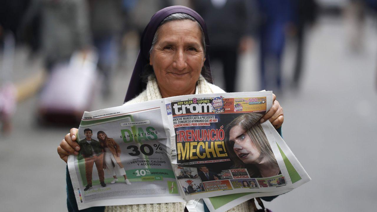 Una mujer sostiene una diario con la noticia de la dimisión de la presidenta interina en la primera página