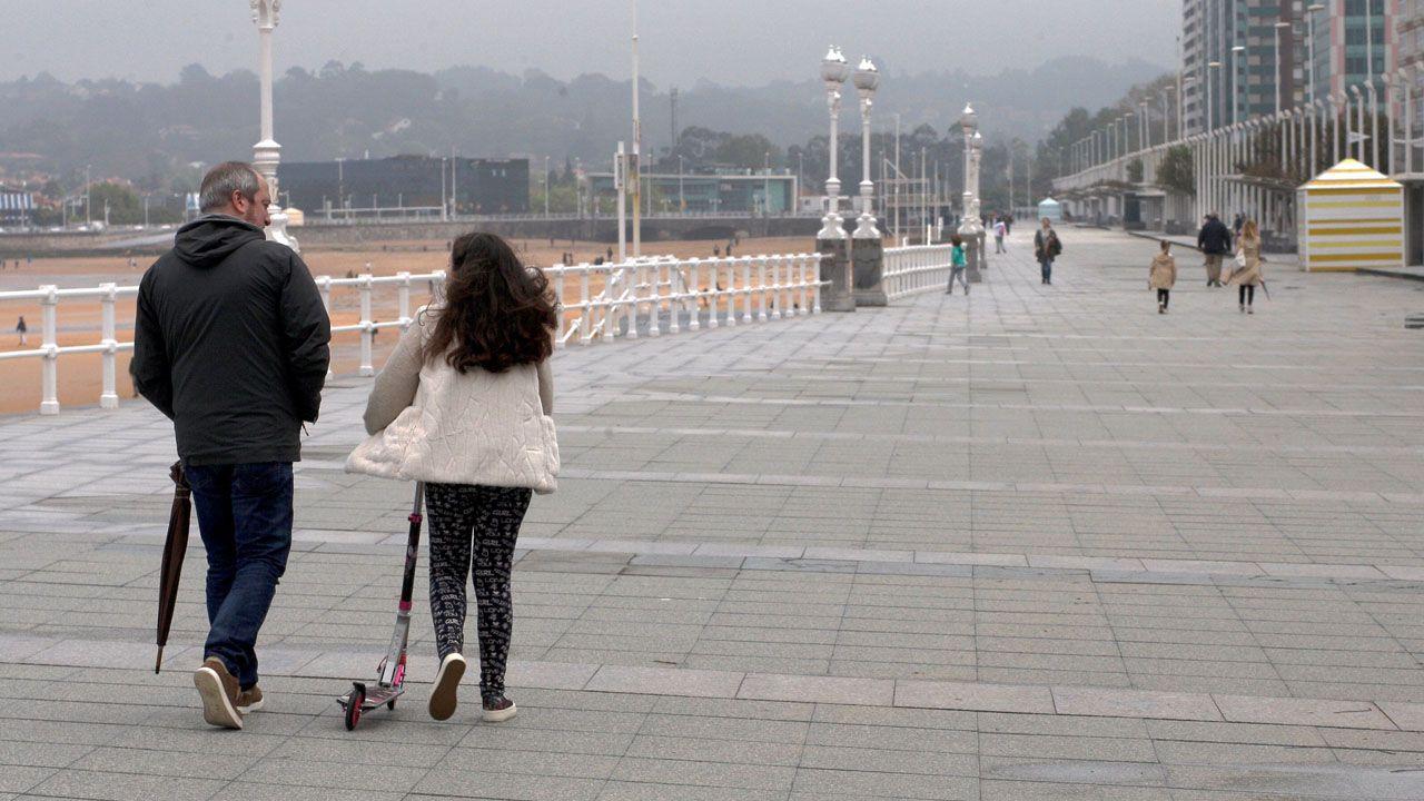Una niña, junto a us patinete, pasea por el paseo de la playa, en Gijón