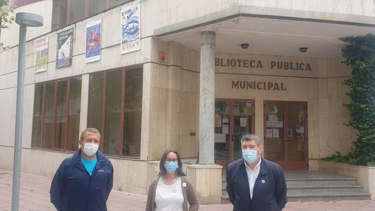José Díaz, concejal de Cultura de Burela, Rocío Rivera, presidenta de la sociedad cultural Ledicia, y Alfredo Llano, alcalde burelense, frente a la Casa da Cultura, donde vieron una exposición de carteles de la Feira do Bonito que en este 2020 ha sido cancelada por la pandemia