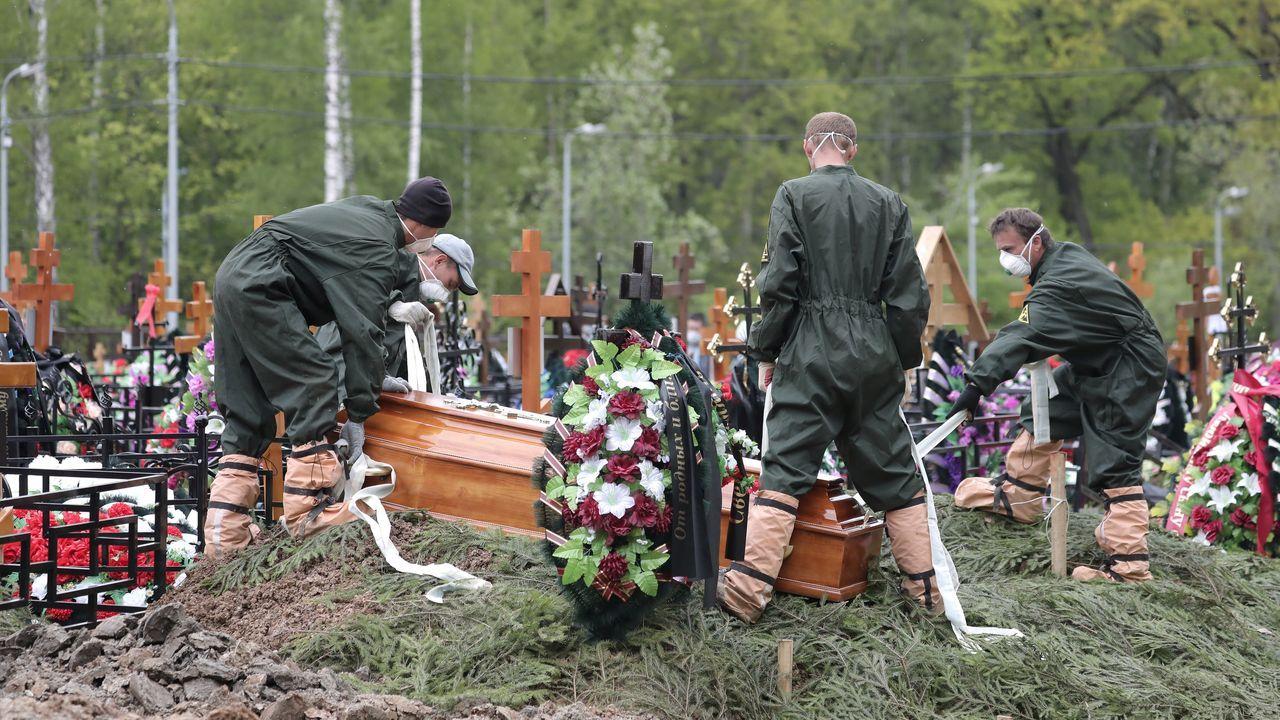 Sepultureros proceden a enterrar a un fallecido por coronavirus en un cementerio moscotiva