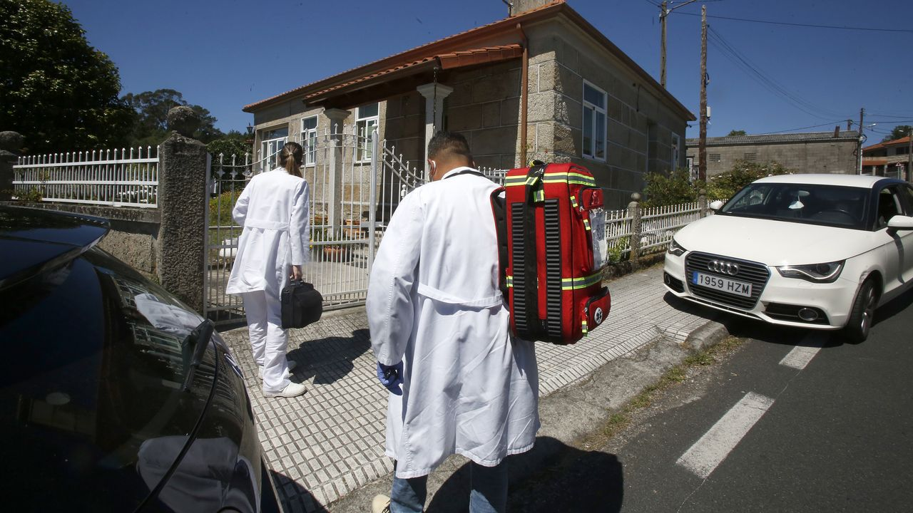 El médico y la enfermera del centro de salud de Piñor llegando a un domicilio con la mochila roja en la que llevan su instrumental