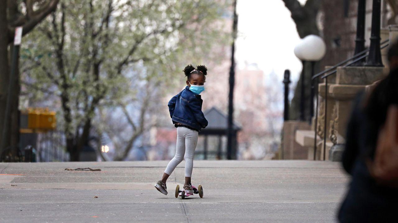 Una niña con mascarilla y un patín en una calle de Nueva YorK